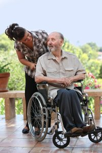elderly man out for walk in wheelchair with grandchild
